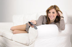 Girl watching TV on sofa having fun Stock Photos