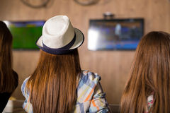 Girl watching tv together in a coffee shop Royalty Free Stock Photos