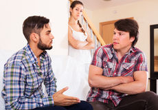 Girl watching two guys arguing indoors Royalty Free Stock Photo