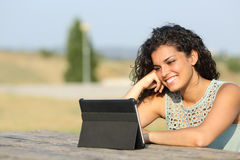 Girl watching video on a tablet outdoors Royalty Free Stock Photography