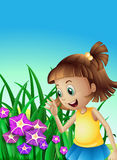 A girl watching the violet flowers in the garden Royalty Free Stock Images