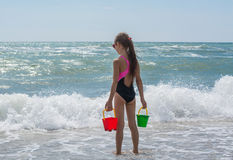 Girl watching the waves from the shore of the sea with toy bucket Royalty Free Stock Images