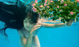 Girl in water. With flowers Royalty Free Stock Images