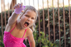 Girl Water Balloon Fight. Girl ready for a water balloon fight, missing teeth royalty free stock images