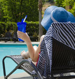 Girl with water bottle by the pool. Girl in blue hat with water bottle by the pool Royalty Free Stock Image