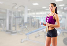 Girl with water bottle and skipping rope at gym club Stock Photography