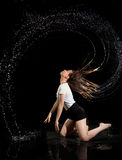 Girl water circle hair black background. Girl in studio on a black background with reflection in the water wearing a white shirt. She creates a circle of water Royalty Free Stock Photography