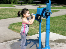 Girl at water fountain. A little girl about to drink from a public water fountain in a park Stock Images