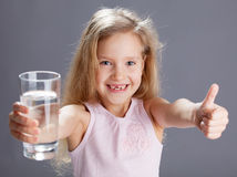 Girl with water from glass Stock Images