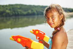 Girl with a water gun in summer Royalty Free Stock Photography