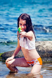 Girl with the water gun. Young girl shoot a water gun in the sea royalty free stock photo