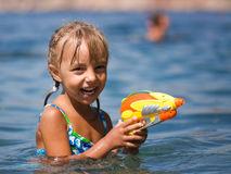 Girl with water pistol. Happy little girl with water pistol has fun in the sea Royalty Free Stock Image