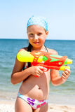 Girl with a water pistol on the beach Stock Images