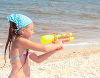 Girl with a water pistol on the beach Royalty Free Stock Photos