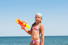 Girl with a water pistol on the beach Stock Photo