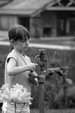 Girl at Water Pump. Girl using old water pump Stock Photo