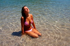 A girl in water on sandy beach Royalty Free Stock Photos