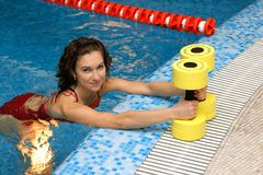 Girl in water, show aqua aerobics dumbbells Royalty Free Stock Images