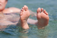 Girl in the water stretches the feet in the air Royalty Free Stock Photography