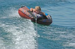 Girl Water Tubes at an Angle. Young girl angles up on a wave on a water tube Royalty Free Stock Images