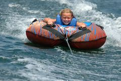 Girl Water Tubing with a Smile. Young girl rides water tube with a big smile on her face Royalty Free Stock Photography