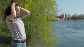 The girl is by the water. Young woman in the fresh air by the river. The wind develops the hair. stock video footage