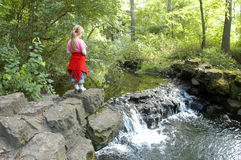 Girl And Waterfall. A young girl pauses by the side of a small waterfall in the middle of the woods Stock Images
