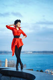 Girl on the waterfront. Attractive girl in red shirt walking along waterfront Royalty Free Stock Photography