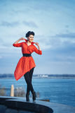 Girl on the waterfront. Attractive girl in red shirt walking along waterfront Royalty Free Stock Images
