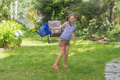 Girl with a watering can Stock Images