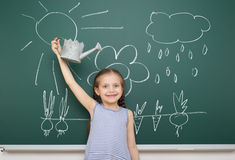 Girl with watering can drawing on school board Stock Photos