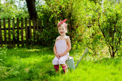 Girl with a watering can in the garden. Little girl with a watering can in the garden royalty free stock photo