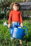 Girl with watering can on the vegetable garden Stock Photos