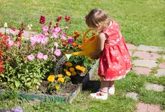 Girl watering flower beds Royalty Free Stock Photos
