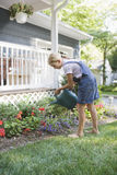 Girl Watering Flowers In The Backyard Stock Photography