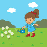 Girl is watering the flowers. Girl watering flowers in the garden Royalty Free Stock Image