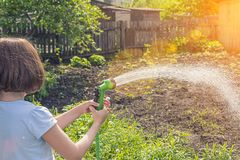Girl watering a garden from a hose royalty free stock photo