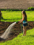 Girl Watering Garden. A young girl watering her familys country garden royalty free stock photos