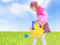 Girl watering the grass. Royalty Free Stock Photography