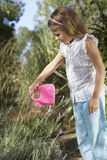 Girl Watering Plant With Plastic Can Royalty Free Stock Photography