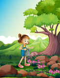 A girl watering the plants near the rocks Royalty Free Stock Images