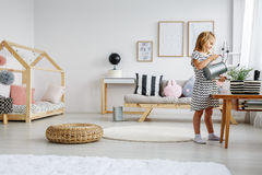 Girl watering plants in room. Young smiling blonde girl watering plants with watering can in cute pastel scandi room Royalty Free Stock Photos