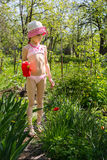 A girl with a watering pot. Helps to water the flowers royalty free stock photo