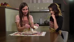 Girl watering vareniki sour cream, slow motion. Two girls are sitting in the kitchen at the table, on a table in a dish of vareniki stock video