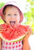 Girl with watermelon. Little girl eating a ripe juicy watermelon in summertime stock photo