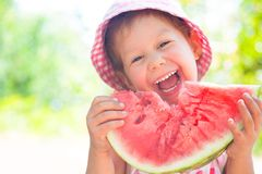 Girl with watermelon. Little girl eating a ripe juicy watermelon in summertime stock photography