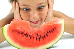 Girl and watermelon. A little girl looking at a slice of watermelon stock photo