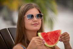 Girl with watermelon under palm tree royalty free stock photo