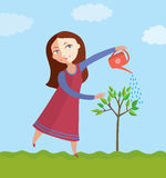 Girl waters a tree. The girl waters a tree in a garden Royalty Free Stock Image