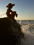 A girl and a waves. A girl with a hat sitting on a rock in the sea at sunset, a wave is just breaking on the rocks royalty free stock images